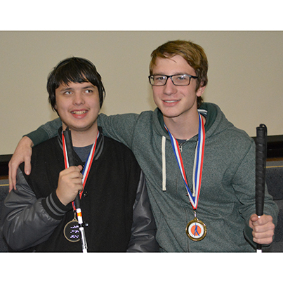 Two smiling young men wear medals and hold while canes used for travel by people who are blind