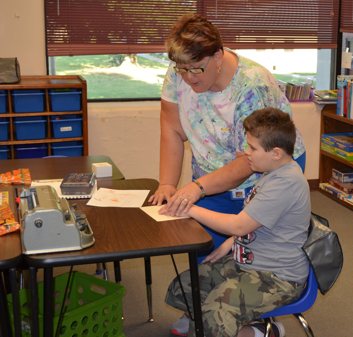 A teacher helps a student read braille