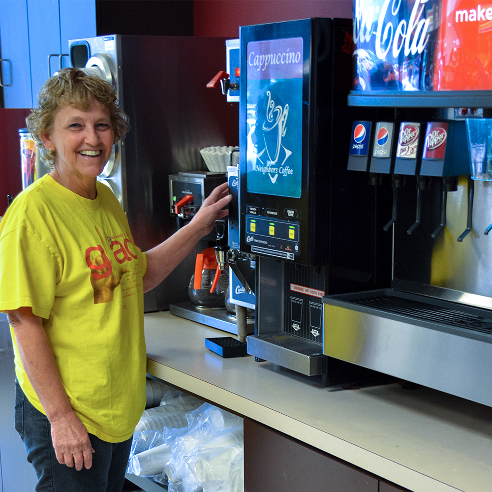a woman stands in from of soda fountain machine