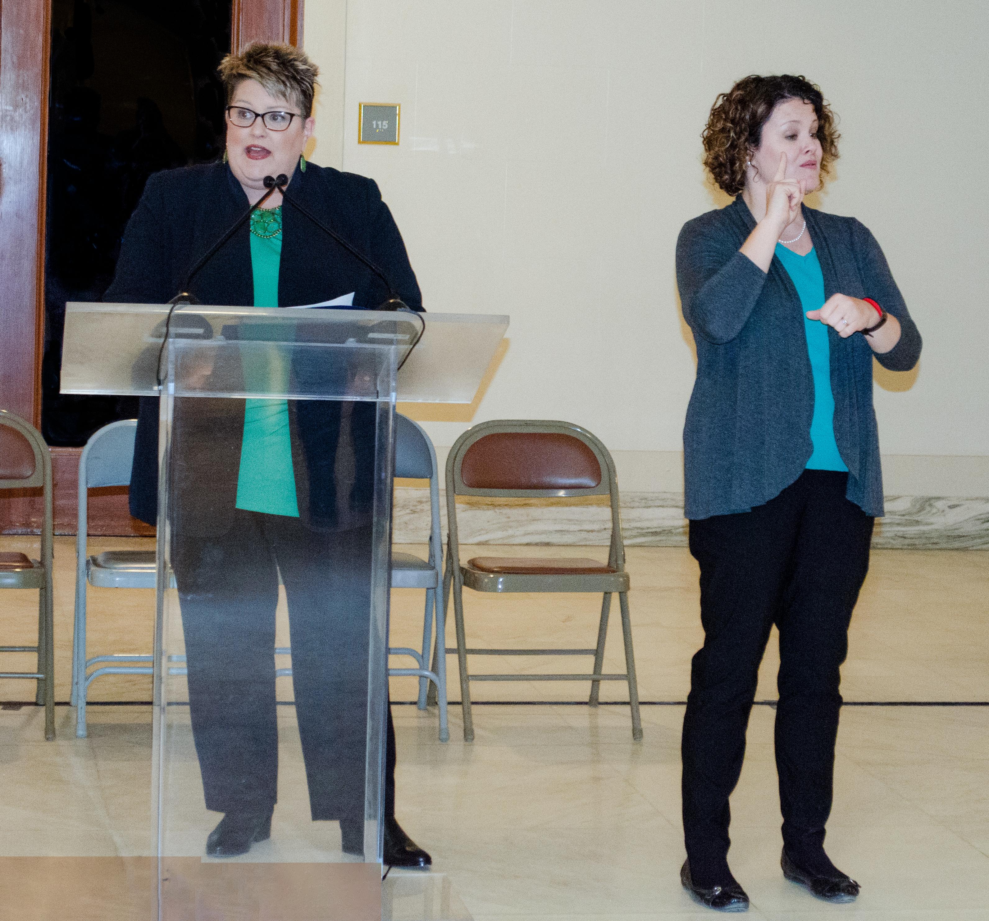 A sign language interpreter signs for Director Fruendt at an event.