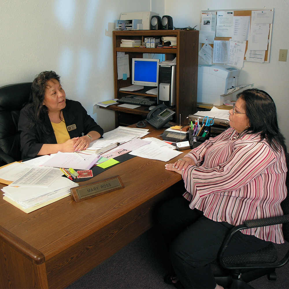 A Native American Counselor sitting at her desk with a Native American woman across from her.