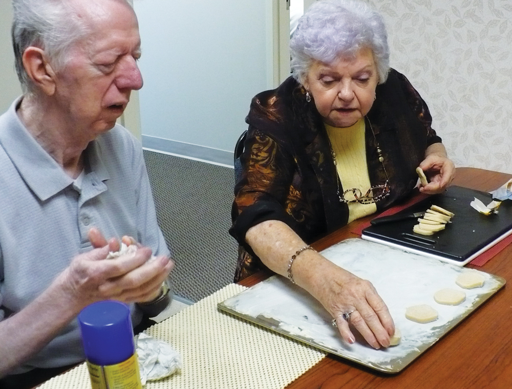 A older man and woman sitting at a table preparing cookies