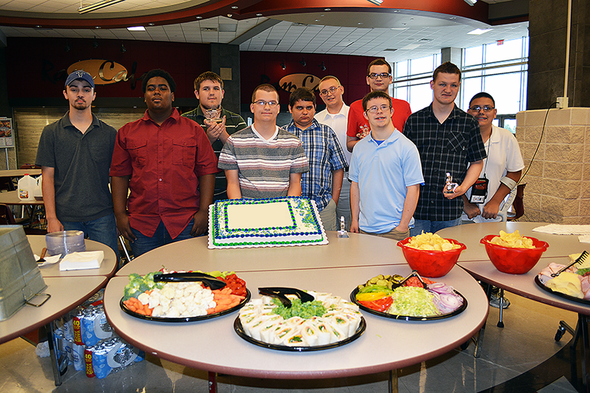 students gathered around a table holding a cake celebrating the program.