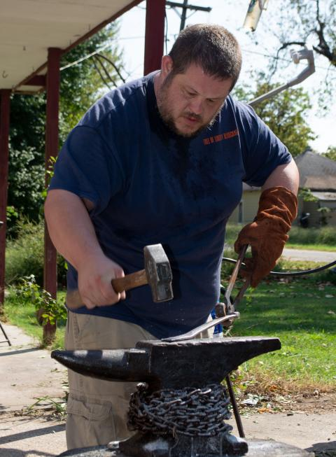 A man using tongs holding hot metal and hammer it on an anvil.