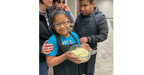 An African American young girl holds a bowl of cole slaw.