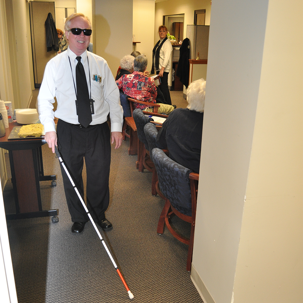 A man is walking with a white cane in an office.