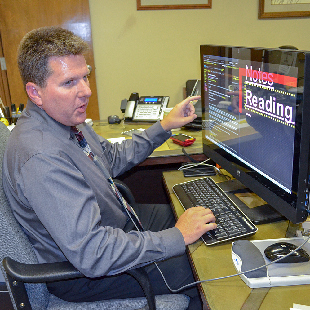 A man using a large computer monitor with a text enlarging software.