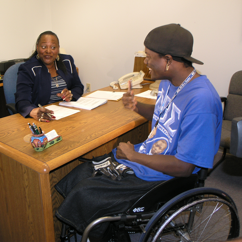 An African American female counselor talks with young African American young man in wheelchair.