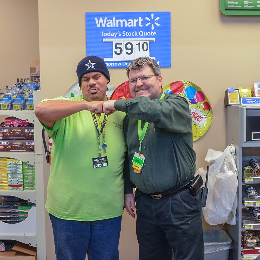 A Walmart manager and an employee with disabilities fist pump for the camera.