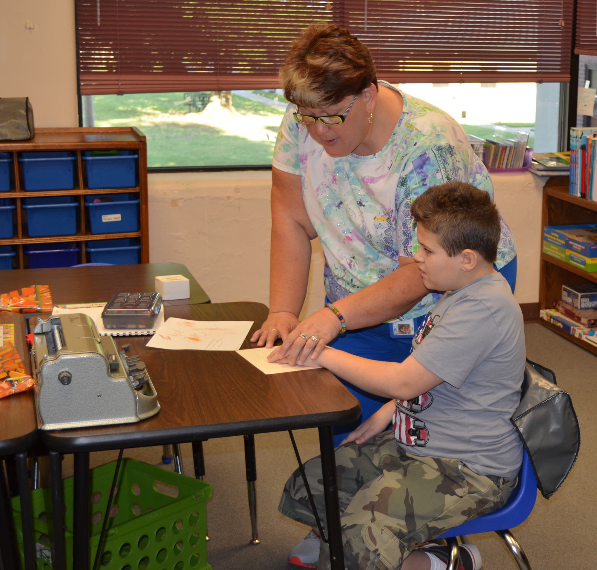 a young boy and teacher go over some Braille