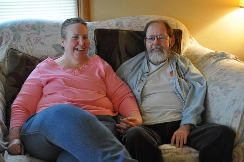 A man and woman sit on a couch holding hands.