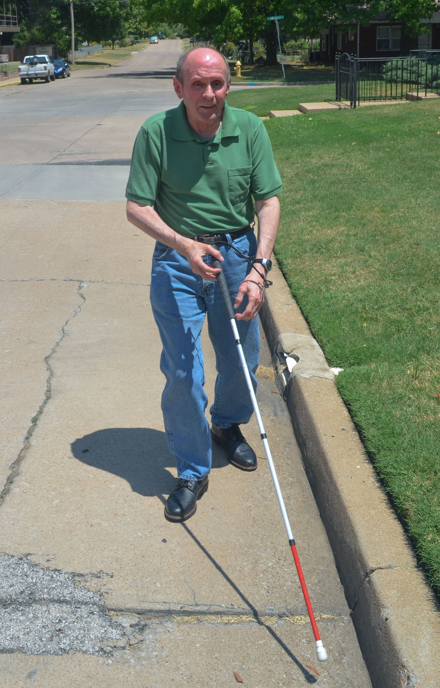 Hill walking up the street using a white cane.