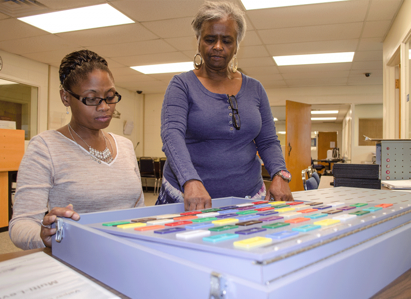 A woman sits at a board with buttons and another woman stands at her side explaining the exercise.