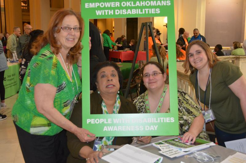 four women hold the People with Disabilities Awareness Day photo frame, three are smiling for the camera and one is make a funny face.