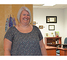 Smiling woman stands in the doorway of an office with a desk and pictures on the wall