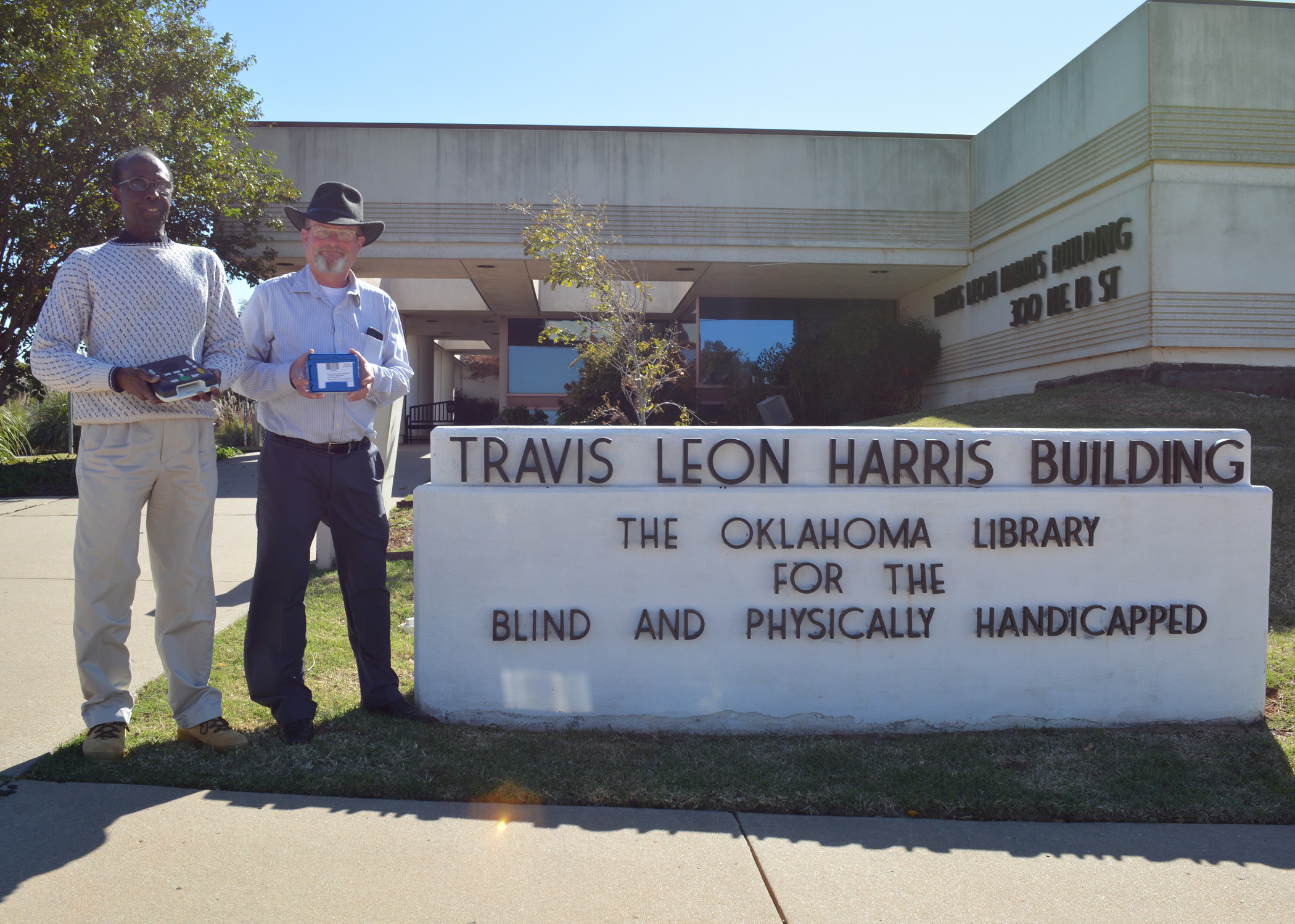 Two men stand in front of a building with a sign Travis Leon Harris Building The Oklahoma Library for the Blind and Physically Handicapped