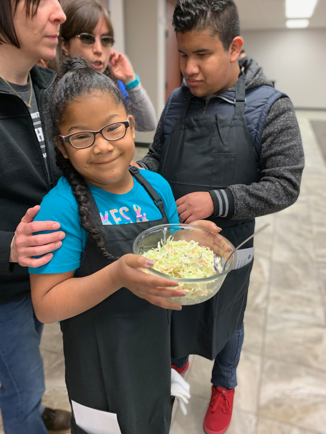 A young girl holds a bowl of spaghetti.