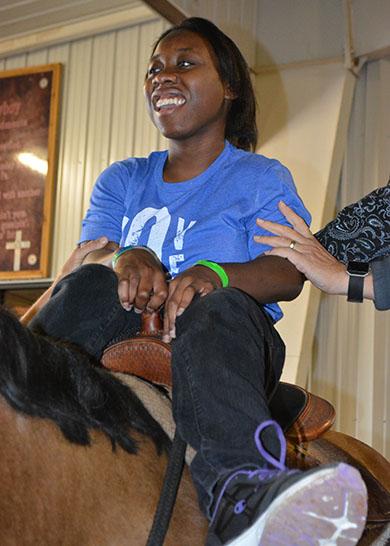 Hands support happy teenage Black girl sitting in saddle on horseback