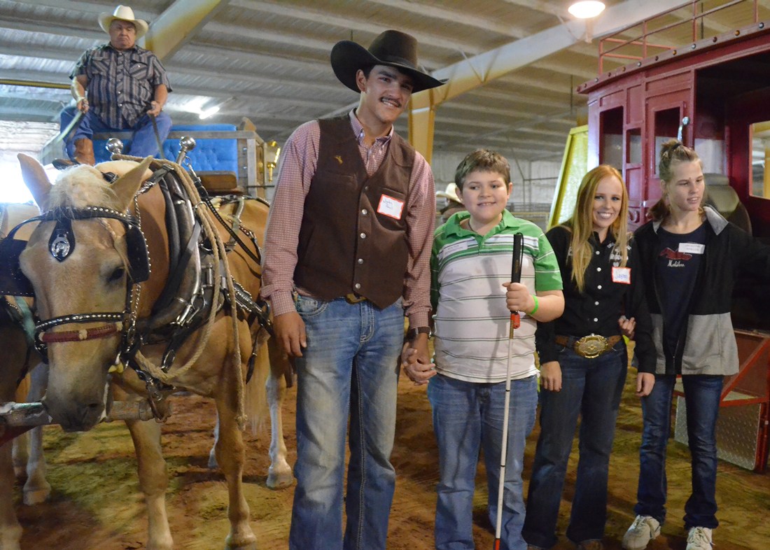 2 cowboys and 1 cowgirl pose with young woman and young man holding a white cane between a horse and wagon and stagecoach