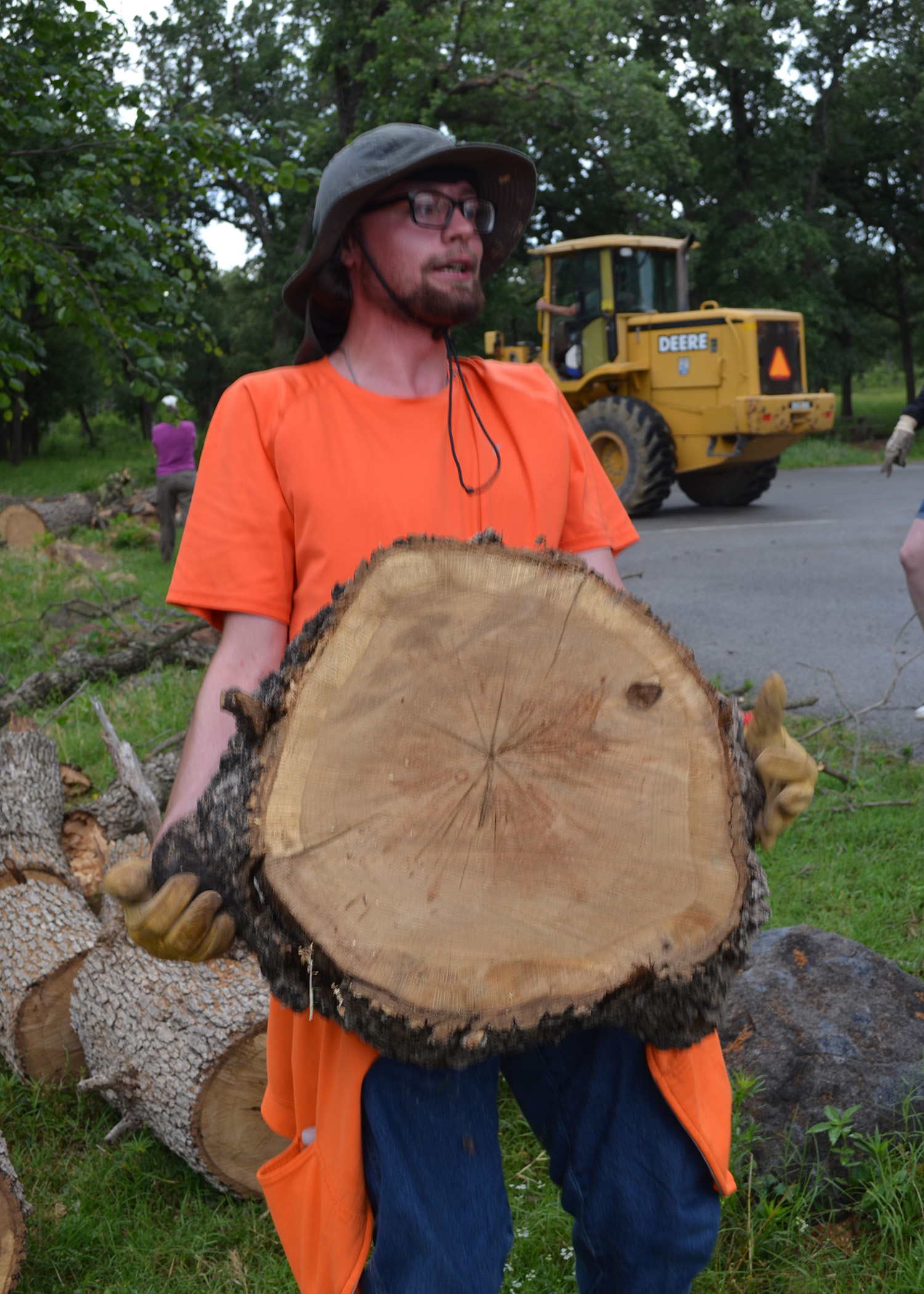 Young man carries slice of tree trunk