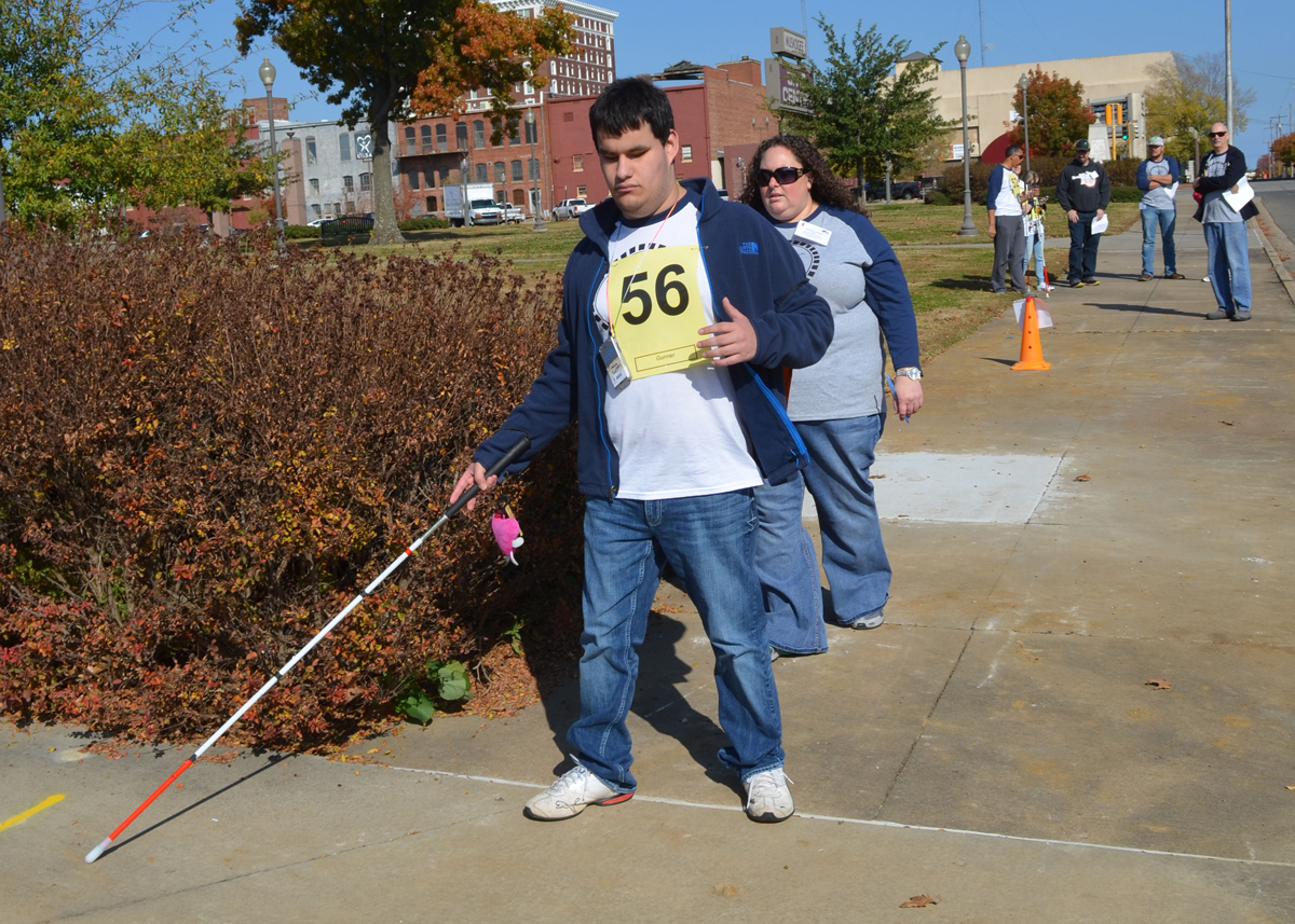 Young man followed by a woman uses white cane travels on sidewalk