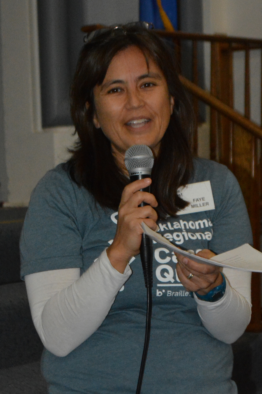 Smiling woman holds a microphone and papers
