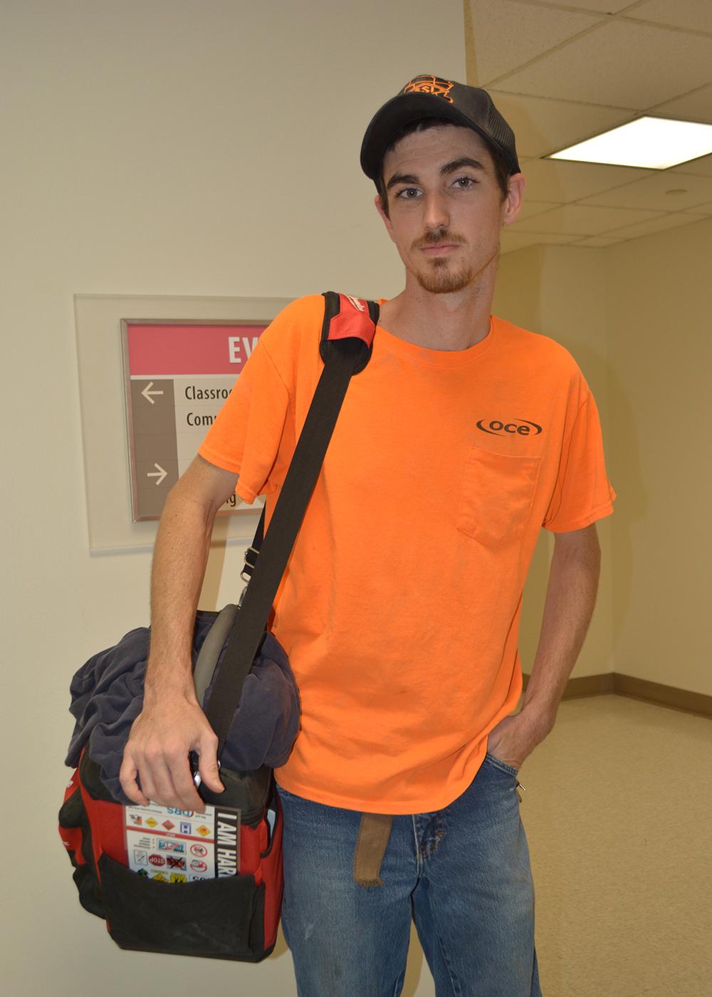Man wearing cap holds a large bag over his shoulder