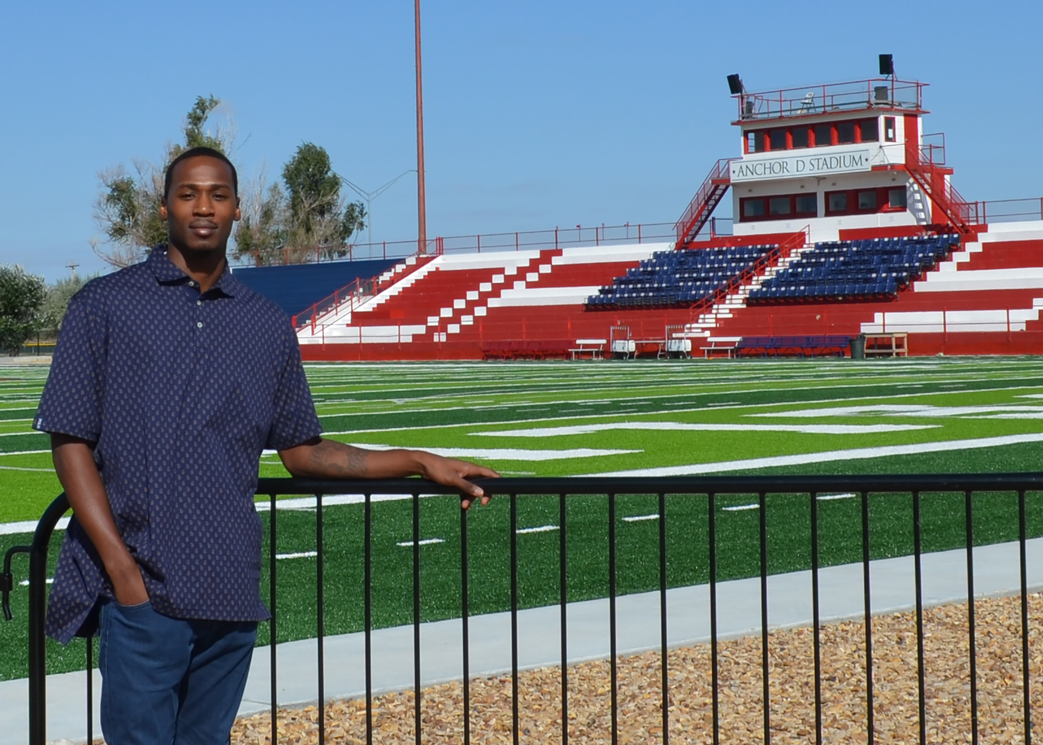 Young man leans on fence in front of football field and stadium