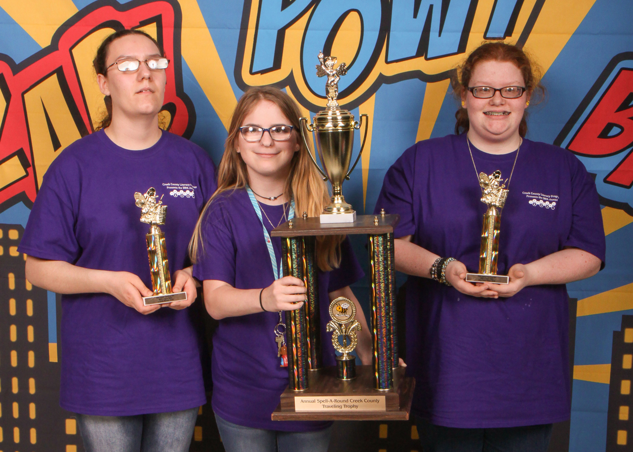 Three young women pose with one very large and two small trophies.