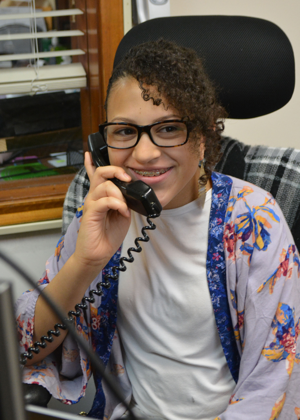 Smiling young woman seated in desk chair talks on the phone
