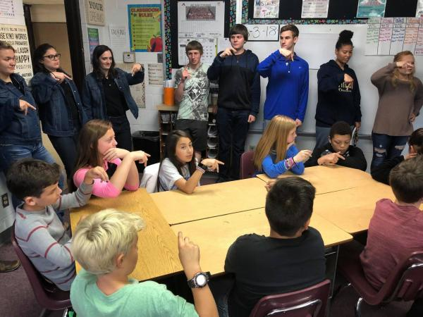 Students standing in a half circle and seated at a table fingerspell signs used to communicate with deaf people.