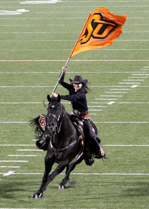 Woman holding OSU flag rides horse on football field.