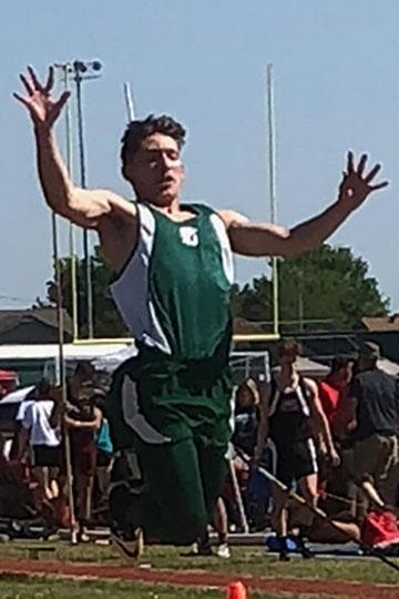Young man in track uniform jumps with outspread arms.