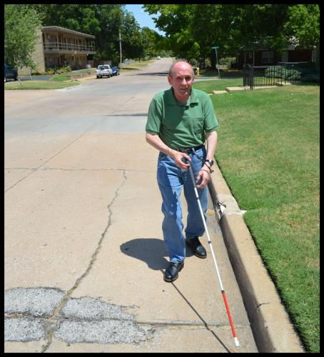 Hill walking up the street using his white cane