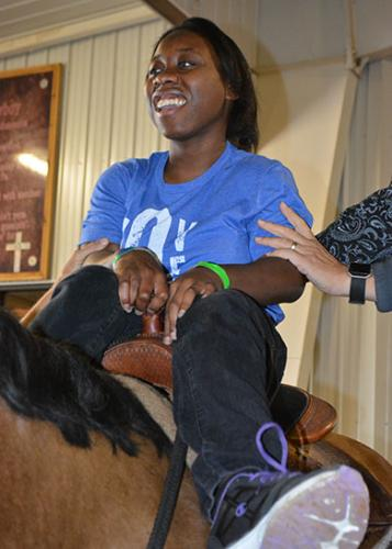 Hands support happy teenage Black girl sitting in saddle on horseback