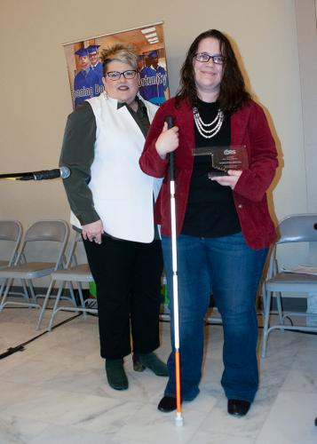 Smiling woman stands beside woman with long white cane holding an award.
