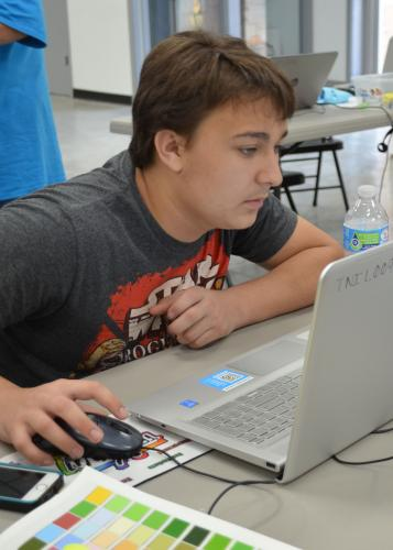 Young man with his hand on a computer mouse looks intently at laptop screen.