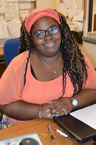 Smiling woman seated at office desk.
