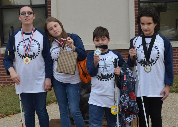 Four young students with white canes display medials