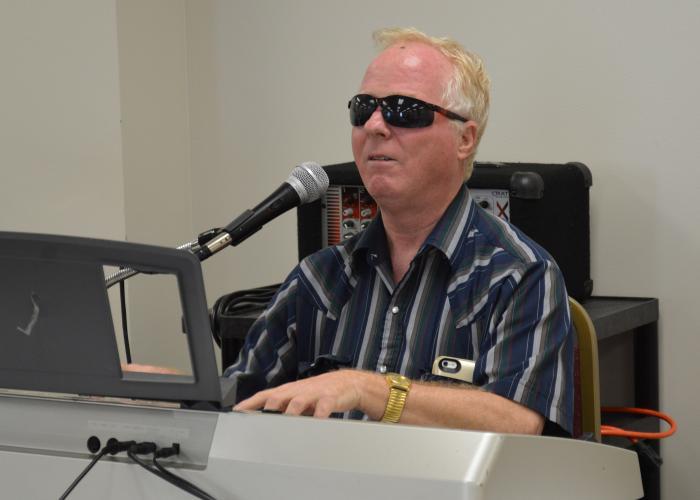 Man wearing sunglasses plays keyboards