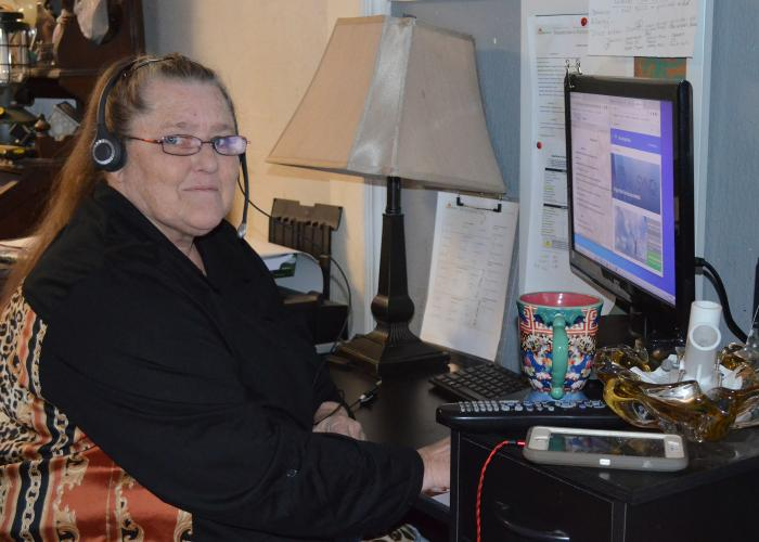Smiling woman sits at desk with laptop, monitor and phone