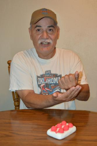 Man uses sign language for the deaf at table with six small balls on rectangular object
