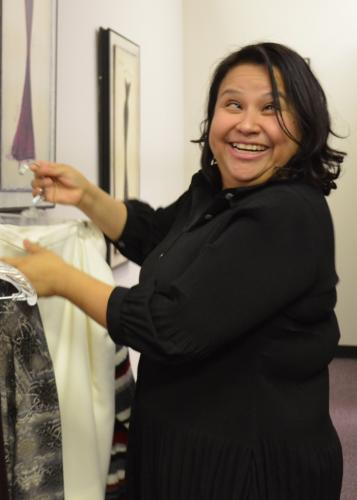 Smiling  woman holds clothing on a hanger.