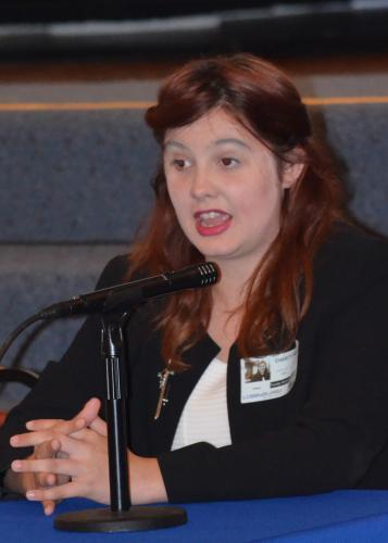 Young woman in business suit speaks into a microphone