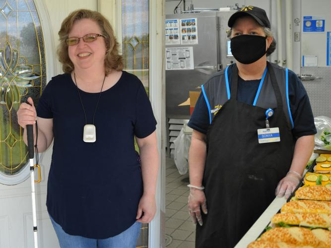 Two photos: Woman holds long white cane. Woman wearing apron and masks stands beside tray of sub sandwiches.