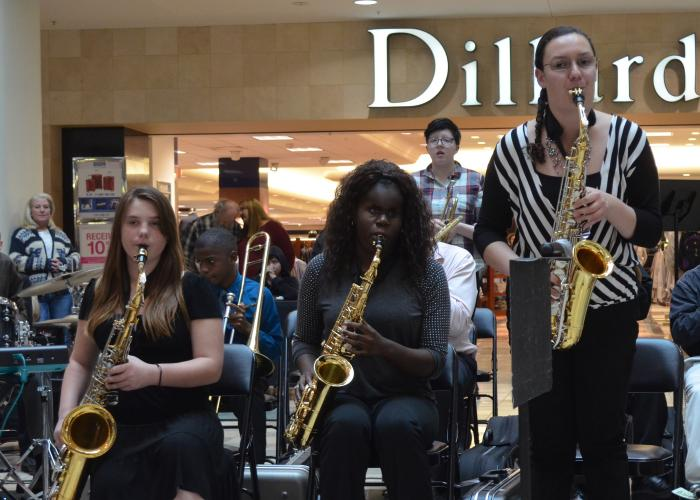 Five students play saxophones in a mall