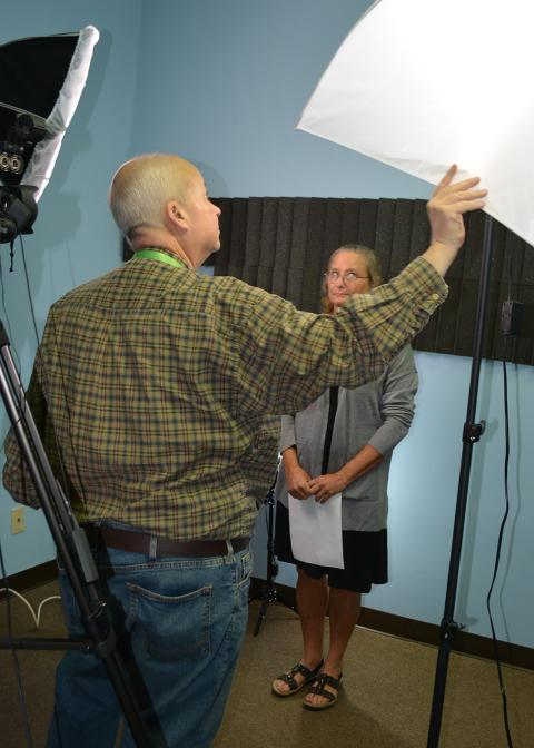 Man adjusts a white shade for woman standing with sheet of paper in hand