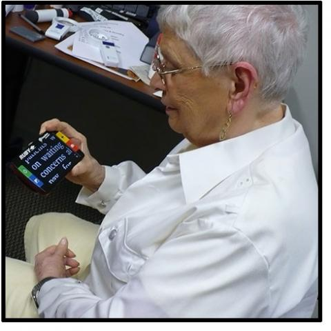 An older woman looking at a handheld device that magifies text