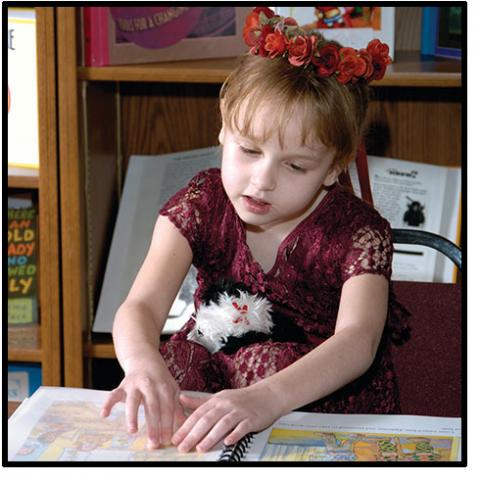 A little girl reads a braille children's book.