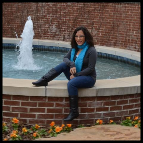 a woman sits on a water fountain edge